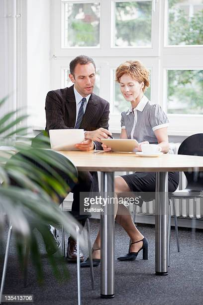 A businessman and businesswoman using a digital tablet in a meeting