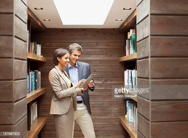 Businessman and businesswoman using digital tablet in office library