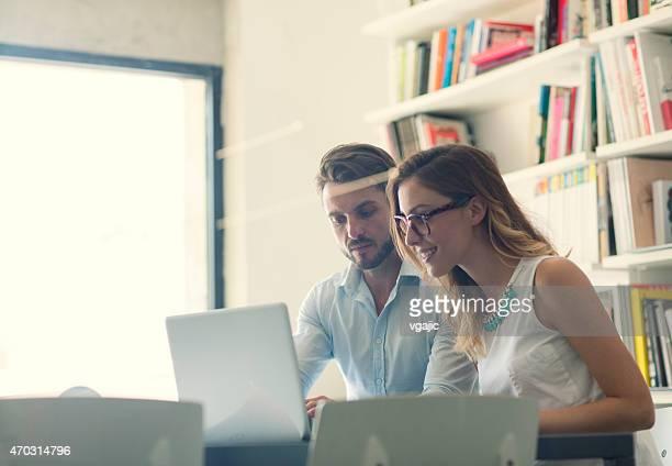 Empresário e Mulher de negócios com computador portátil em um escritório.