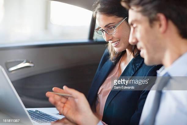 Geschäftsmann und Geschäftsfrau mit laptop im Rücksitz des Autos