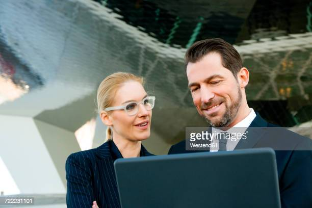 Businessman and businesswoman using laptop outdoors