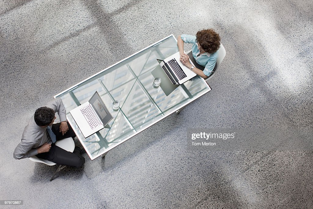 Businessman and businesswoman using laptops at table : Stock Photo