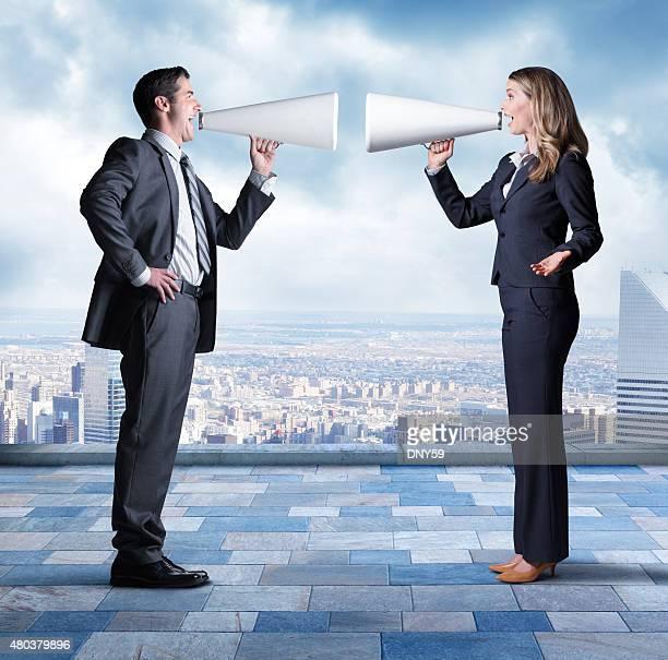 Geschäftsmann und Geschäftsfrau mit Megaphones, zu schreien an jedem anderen