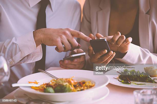 Businessman and businesswoman using phones on lunch