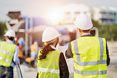 Businessman and businesswoman using see plan paper at construction site