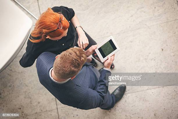 Businessman and businesswoman using tablet pc in lobby overhead