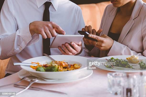 Geschäftsmann und Geschäftsfrau auf Mittagessen mit Technologien