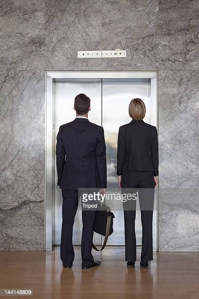 Businessman and Businesswoman waiting for elevator