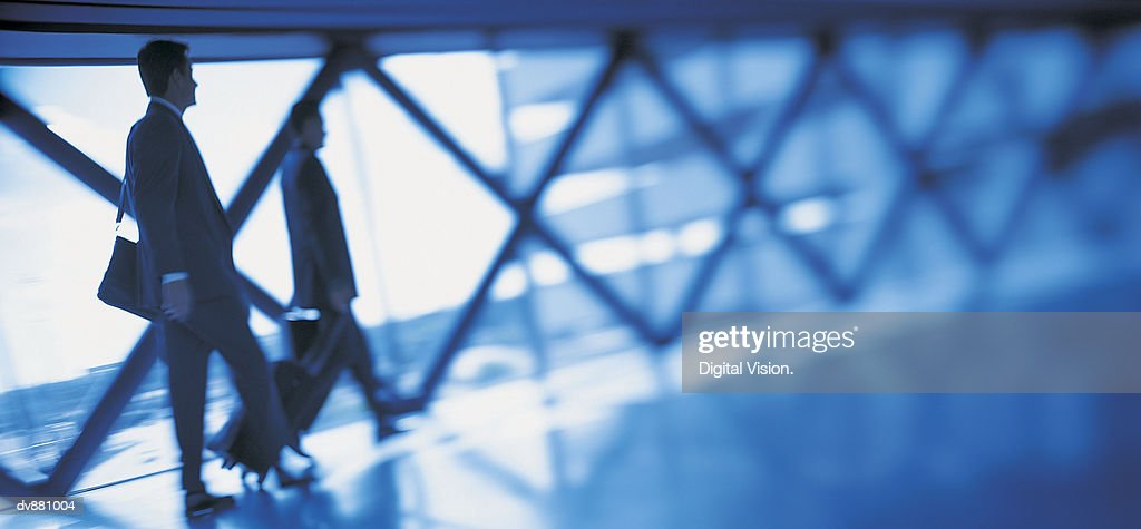 Businessman and Businesswoman Walking Along a Concourse : Stock Photo