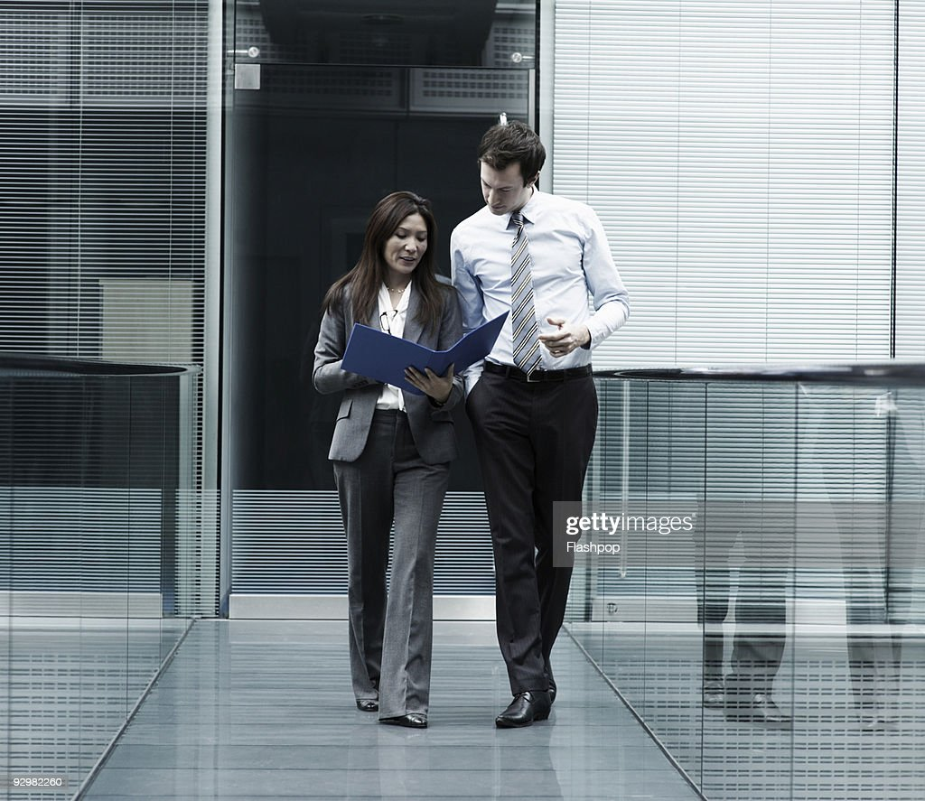 Businessman and businesswoman walking and talking