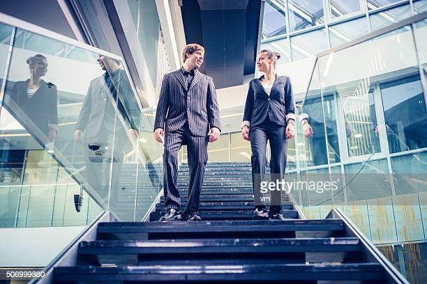 Homme d'affaires et femme d'affaires marche dans les escaliers et discuter