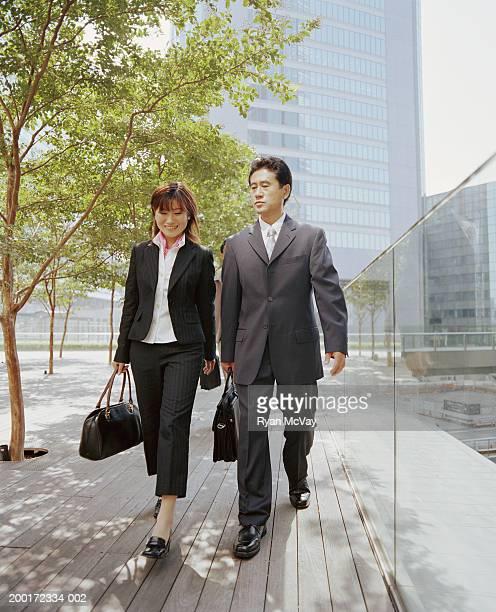 Businessman and businesswoman walking, having conversation