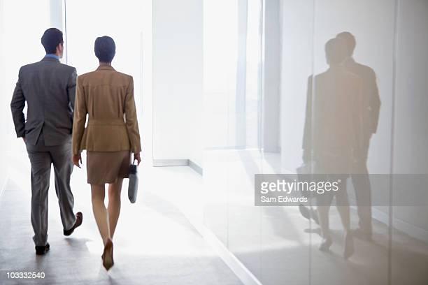 Businessman and businesswoman walking in corridor