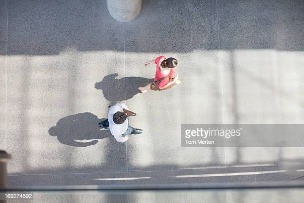 Businessman and businesswoman walking on sidewalk