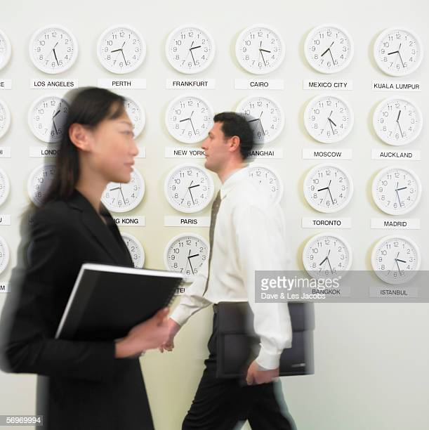 Businessman and businesswoman walking with time zone clocks on the wall behind them