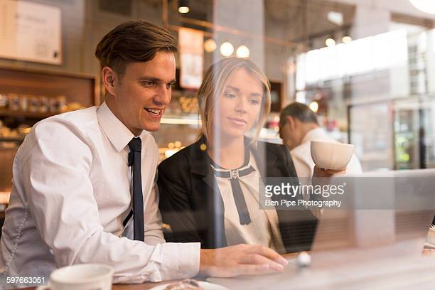 Businessman and businesswoman working on laptop in cafe