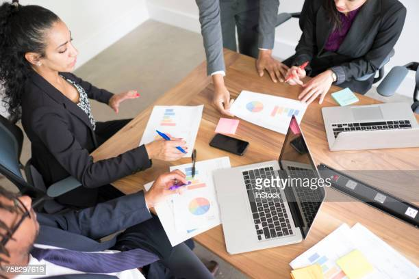 Businessman and businesswomen, in office, using laptops