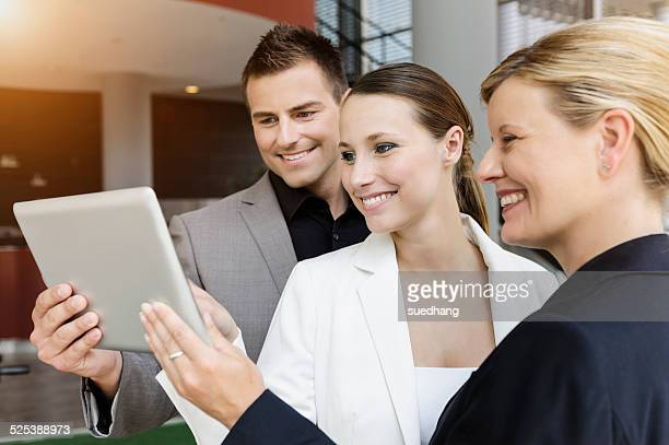 Businessman and businesswomen sharing information on digital tablet