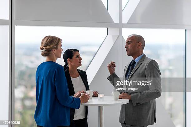 Businessman and businesswomen talking while drinking coffee