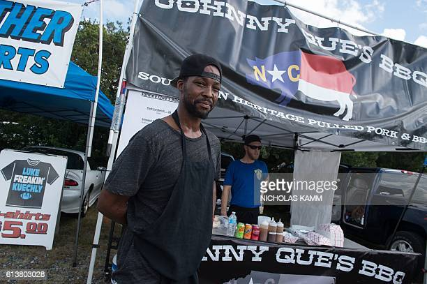 Businessman and chef Santi Jones poses in front of his barbeque stand offering barbeque pork tacos to tailgaters in a parking lot near Bank of...