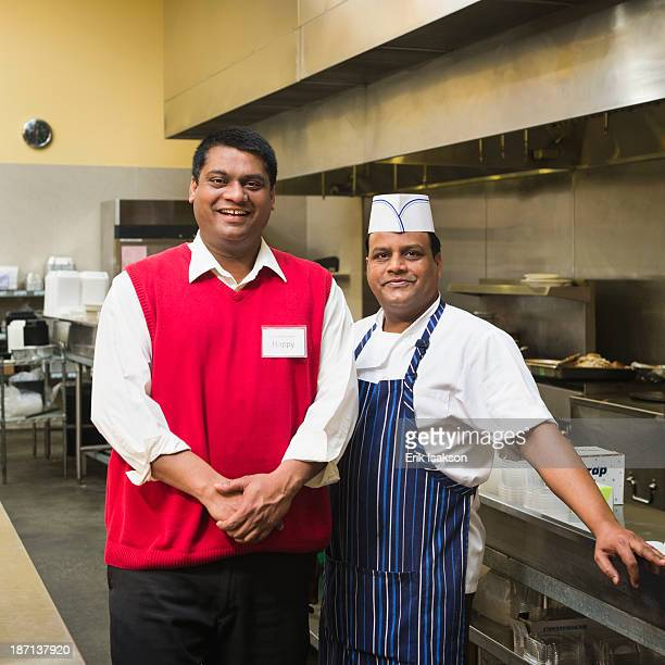 Businessman and chef standing in kitchen