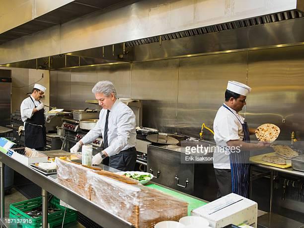 Businessman and chefs working in kitchen