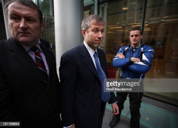 Businessman and Chelsea Football Club owner Roman Abramovich is surrounded by his security team as he leaves The High Court at The High Court on...