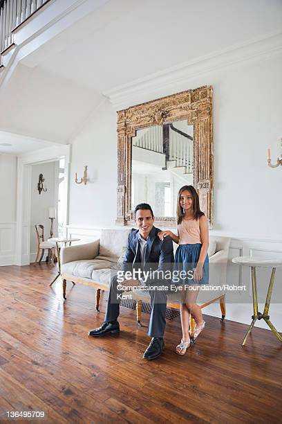 Businessman and daughter in living room, smiling