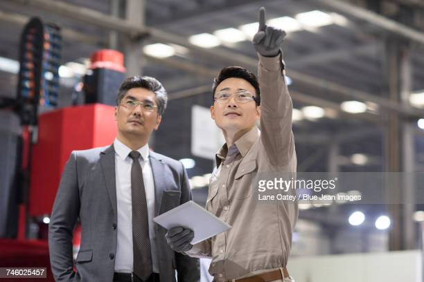 Businessman and engineer talking in the factory