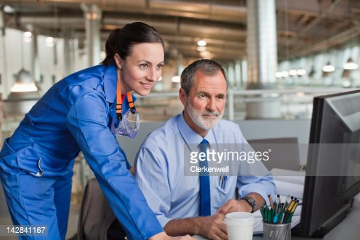 Businessman and engineer using computer in factory : Stock Photo