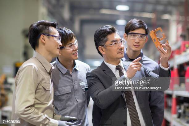 Businessman and engineers checking machine parts in the factory