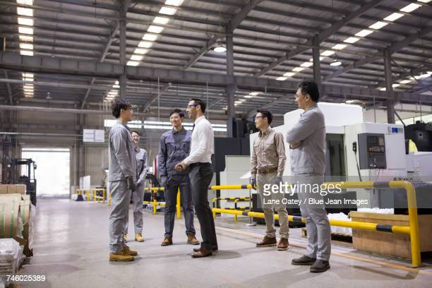 Businessman and engineers talking in the factory