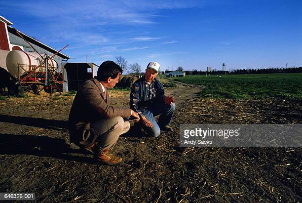 Businessman and farmer consulting at field edge,background buildings