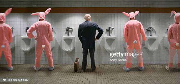 Businessman and four men wearing rabbit costume standing at urinal, rear view (digital composite)