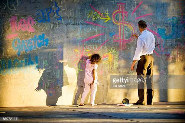 businessman and girl making chalk graffiti