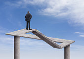 Rear view of businessman standing and looking on the impossible staircase with cloudy sky background. He is looking further, thinking and searching new ideas. Digitally generated image inspired Escher