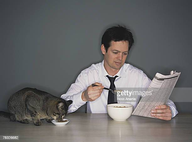 Businessman and pet cat having breakfast together