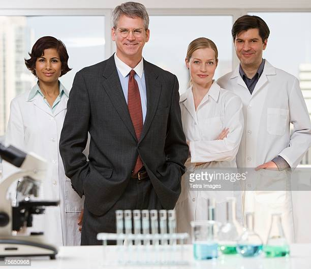 Businessman and scientists in laboratory