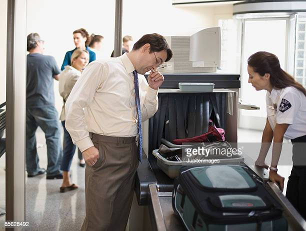 Businessman and security officer at airport security checkpoint