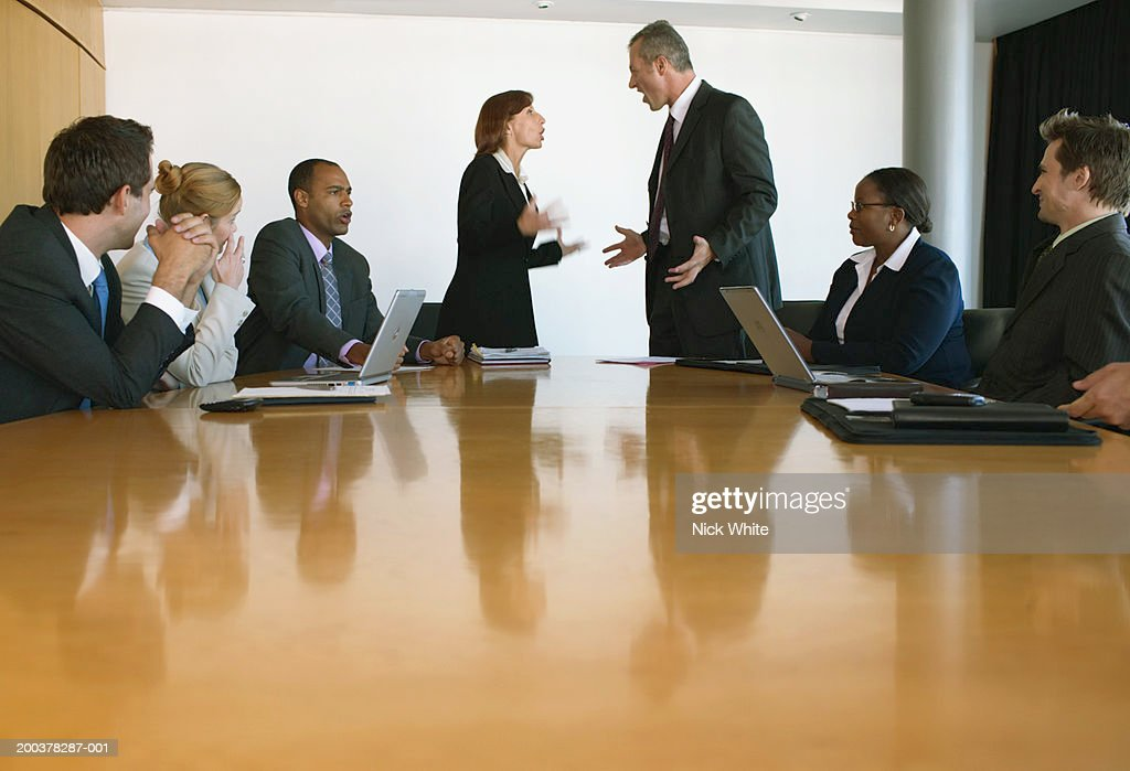 Businessman and woman arguing in conference room, colleagues watching