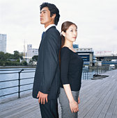 Businessman and woman back to back on bridge, side view