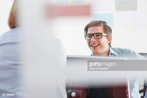 Businessman and woman chatting in office