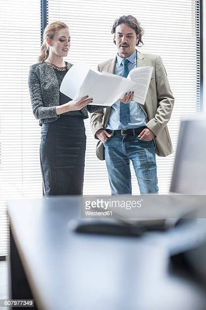 Businessman and woman discussing documents at the window