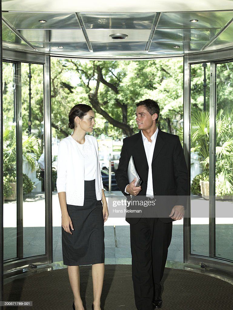 Businessman and woman entering office building : Stock Photo
