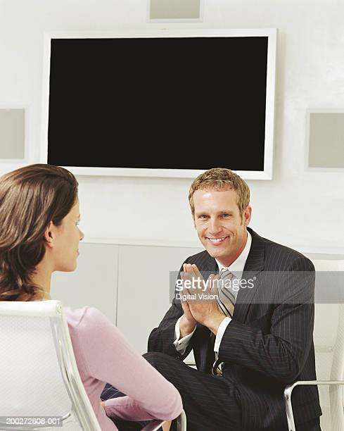 Businessman and woman in video conference room, portrait of man