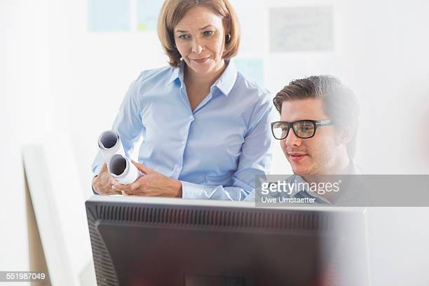 Businessman and woman looking at computer at office desk