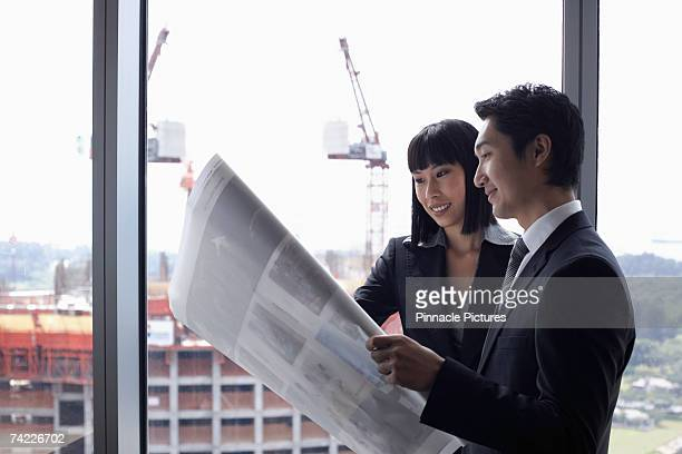 Businessman and woman looking at plans in front of window, waist up