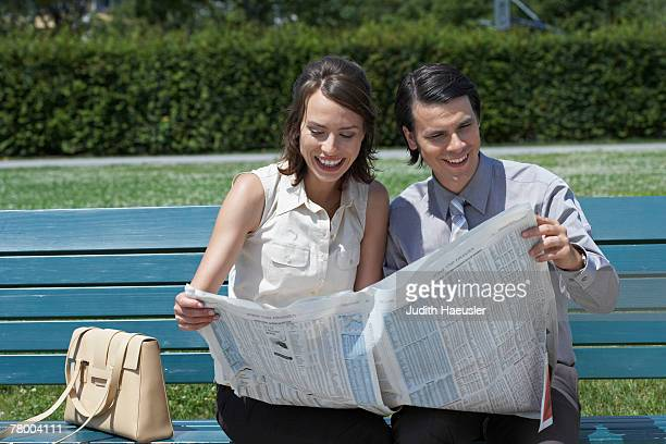 Businessman and woman on bench in park reading a newspaper together smiling.