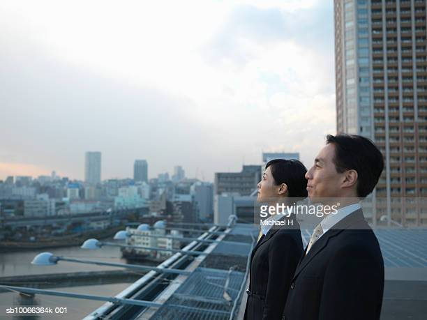 Businessman and woman on roof top looking away, side view