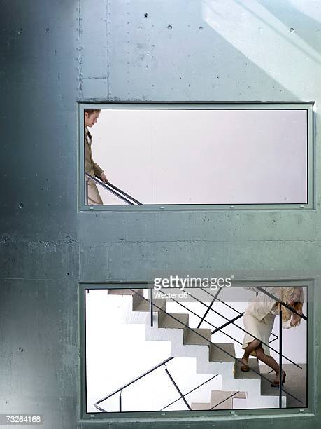 Businessman and woman on staircase, woman peeking